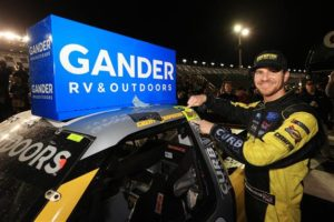 Grant Enfinger affixes the winner's decal on his car in Victory Lane after winning the NASCAR Gander RV & Outdoors Truck Series NextEra Energy 250 at Daytona International Speedway. [Credit: Chris Graythen/Getty Images]