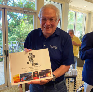 """Bill Warner with his book  'The Other Side of The Fence"""".  [Eddie LePine Photo]"""