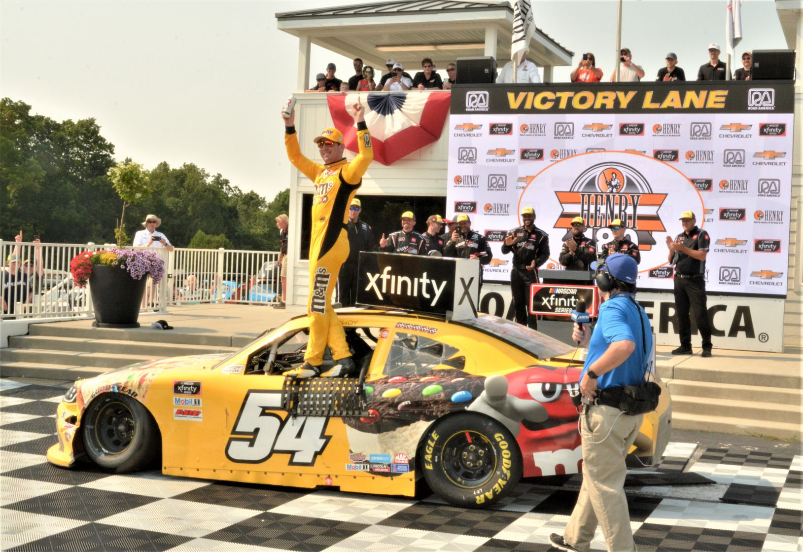 """#54 Kyle Busch - - M&M Ice Cream (Toyota Supra) winner of 12th annual HENRY """"180"""" Nascar Xfinity Series -Road America on 7/3/21. Kyle does a little celebrating on door of car. [Dave Jensen Photo]"""